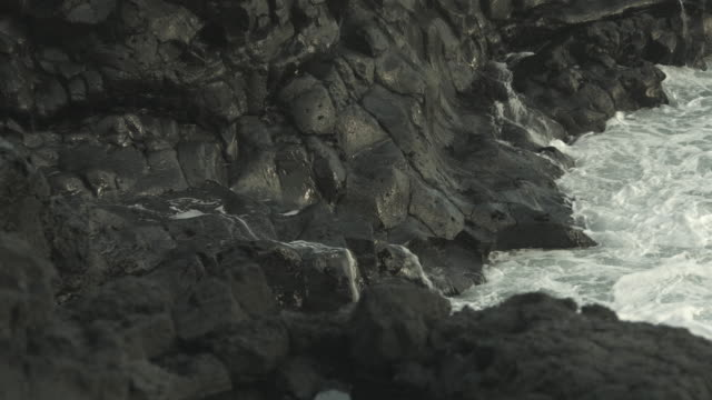 waves roll onto basalt rocks on the coast of iceland.  - basalt stock videos & royalty-free footage