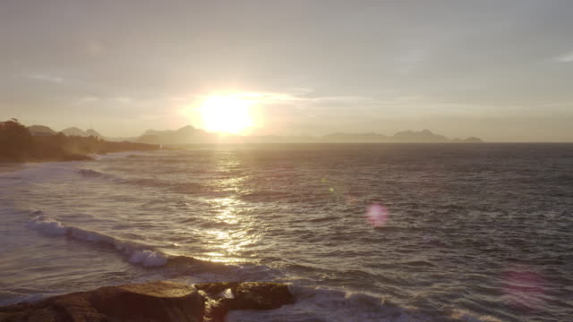 waves roll onto ipanema beach during sunset in rio de janeiro. - riva dell'acqua video stock e b–roll