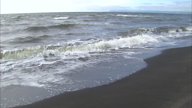 waves roll onto the ishikari coast in hokkaido, japan. - riva dell'acqua video stock e b–roll
