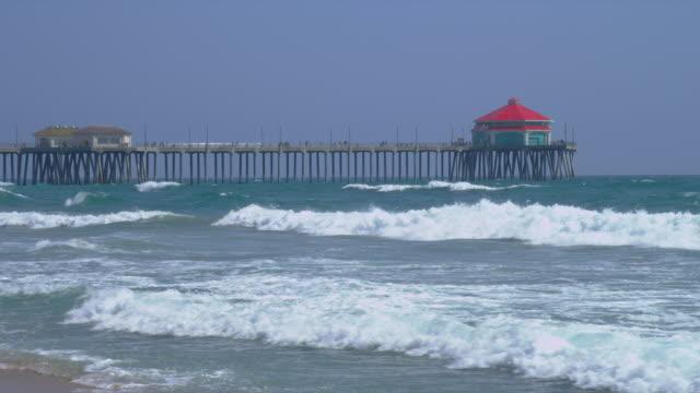 waves roll past the huntington beach pier. - huntington beach california stock videos and b-roll footage