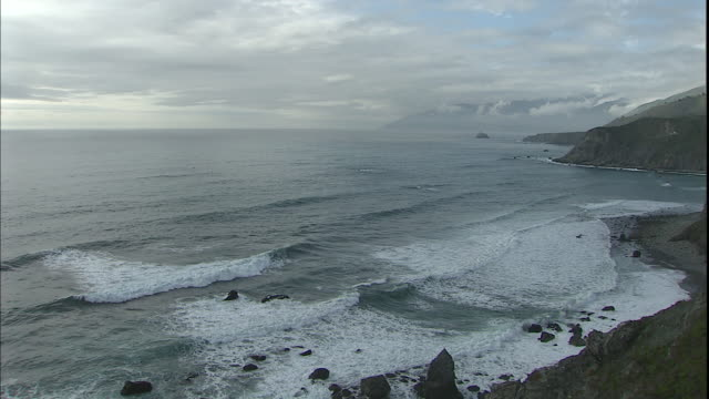 Waves roll up onto a beautiful, rocky coastline.