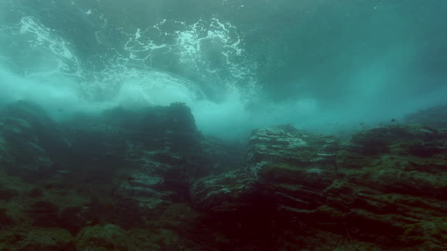 Waves rolling into rocks, underwater shot