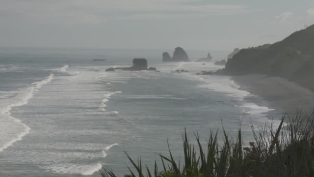Waves rolling onshore at black sand beach West Coast New Zealand
