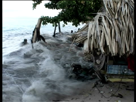 waves rolling under thatched house on stilts, kiribati, central pacific. - flood stock videos & royalty-free footage