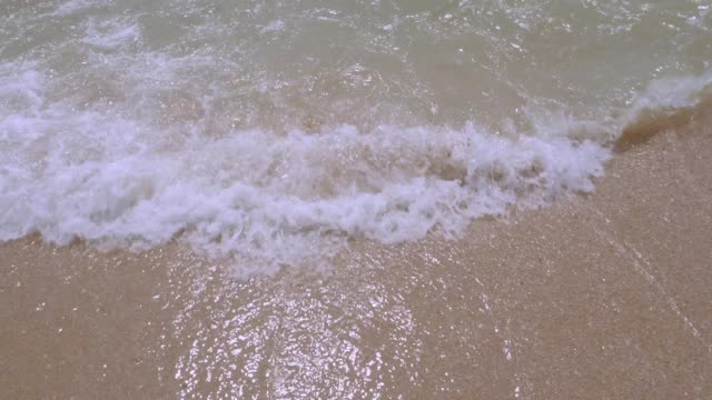 vídeos de stock e filmes b-roll de waves rolling up sand beach. - rolar