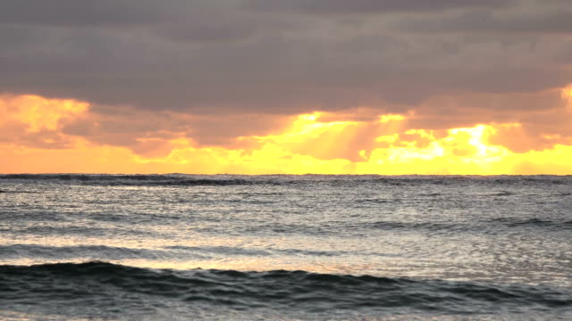 waves slowly washing over kauai island beach with sunset above - butte rocky outcrop stock videos & royalty-free footage