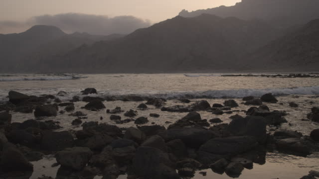 waves splash onto rocky beach at sunset, oman - golfstaaten stock-videos und b-roll-filmmaterial