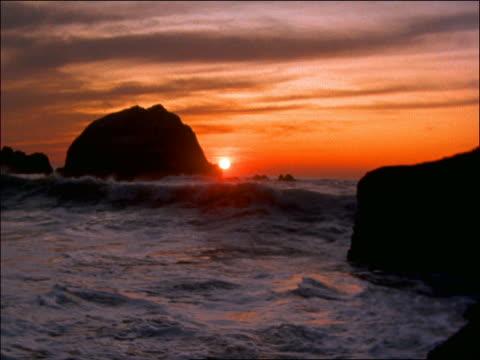 waves splashing against rocks in ocean at sunset / north of san francisco, california - romantische stimmung stock-videos und b-roll-filmmaterial