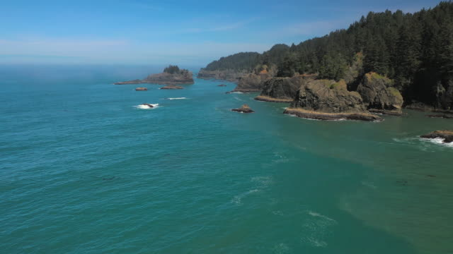 waves splashing at rocky coastline in sea against blue sky on sunny day - southern coast, oregon - pacific northwest usa stock videos & royalty-free footage