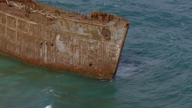 Waves splashing on rusty shipwreck in shallow Pacific Ocean near Hawaii.