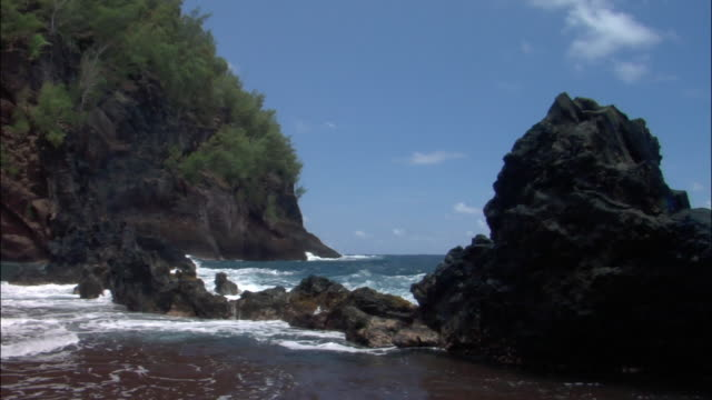 waves splashing over rocks in cove / maui, hawaii - bay of water stock-videos und b-roll-filmmaterial