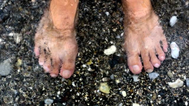 Waves splashing water on man's feet by the sea