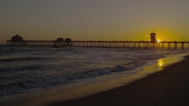 waves was onto a beach near huntington beach pier. - huntington beach california stock videos and b-roll footage