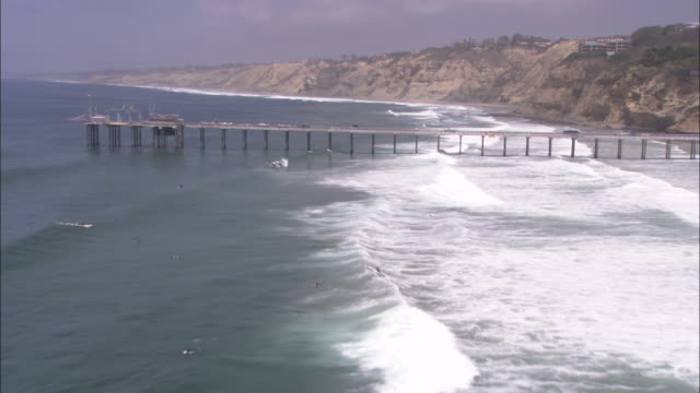 Waves wash around a beach and onto a rocky coast.