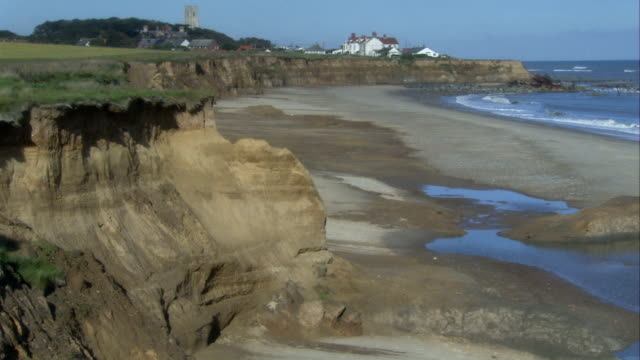 Waves wash away the coast around the village of Happisburgh. Available in HD.