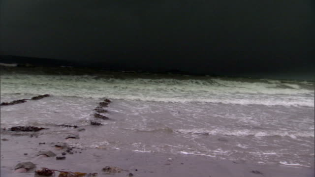 waves wash onto a sandy shore. available in hd. - atlantic ocean stock videos and b-roll footage