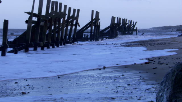 Waves wash past coastal fencing and onto a beach. Available in HD.