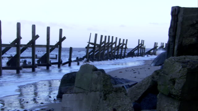 Waves wash past fencing along the coast of Happisburgh Available in HD.
