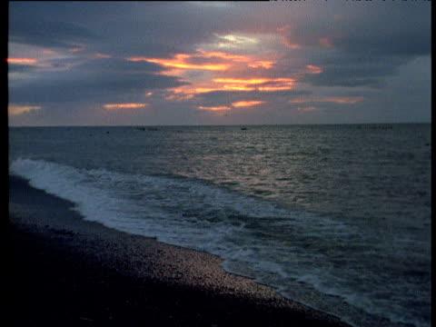 Waves wash up against shore at sunset, Siberia