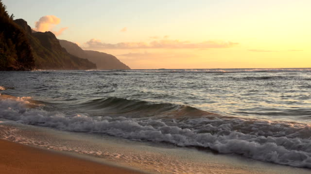 waves washing on beach under sunset sky on kauai island - butte rocky outcrop stock videos & royalty-free footage