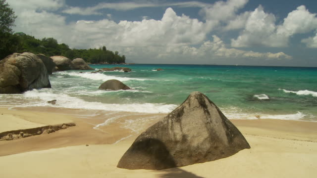 slo mo ws waves washing onto beach with boulders / seychelles - seychelles stock videos & royalty-free footage