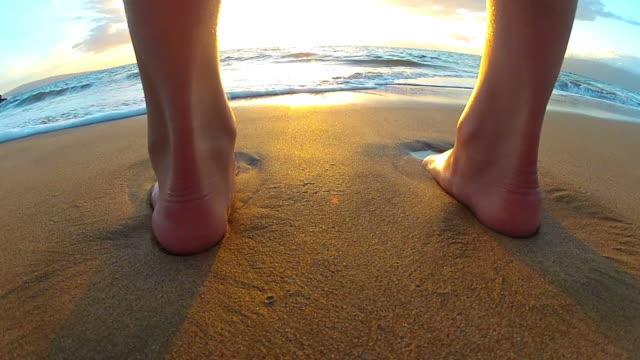 Wellen waschen über junge Mädchen zu Fuß am Strand