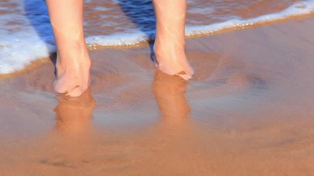 ウェイブズ洗浄若い女性の足をビーチで - 人間の関節点の映像素材/bロール