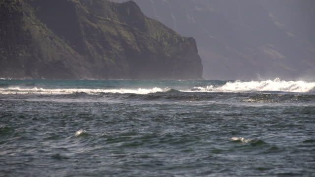 waves washing toward mountains on kauai island - butte rocky outcrop stock videos & royalty-free footage