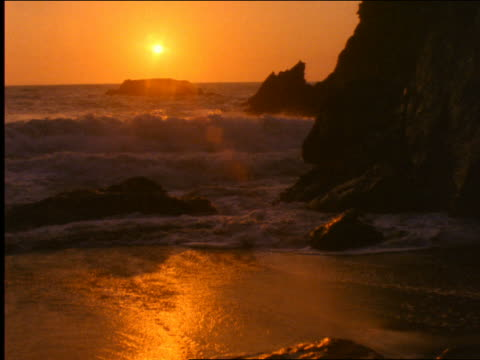 vídeos de stock, filmes e b-roll de waves washing up on deserted beach at sunset / pacific ocean, california - 2001