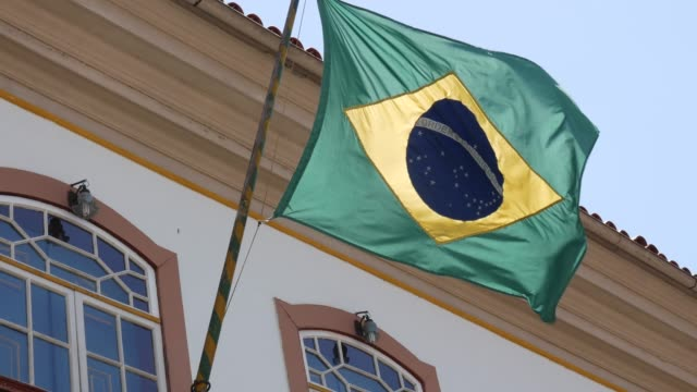 waving brazilian flag from a colonial house in ouro preto, brazil - preto stock videos & royalty-free footage