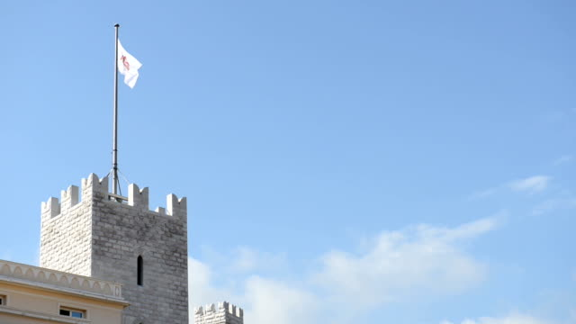 Waving flag on the top of Prince's Palace against cloudy mountains during a hot summer day