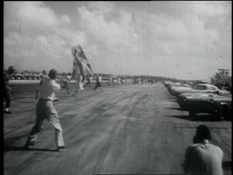 vidéos et rushes de 1957 montage waving of a flag sets drivers into motion as they run to their cars in road race / nassau, bahamas - 1957