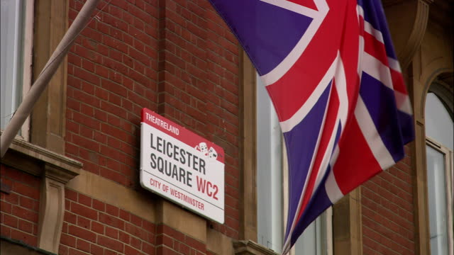 waving united kingdom flag on pole and leicester square wc2 sign mounted to brick building . - leicester square stock videos & royalty-free footage