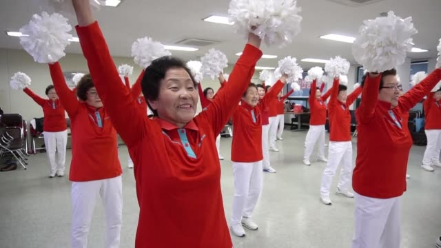 Waving white pom poms in the air dozens of grey haired cheerleaders in matching red and white uniforms hop and skip to Kpop music that fills the...