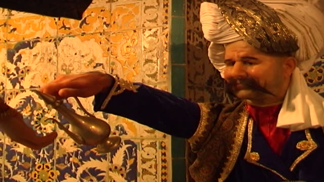 of wax figurine of turbaned attendant in traditional clothing pouring oil into the hand of a patron in a safavid era bath house. - paintings stock videos & royalty-free footage