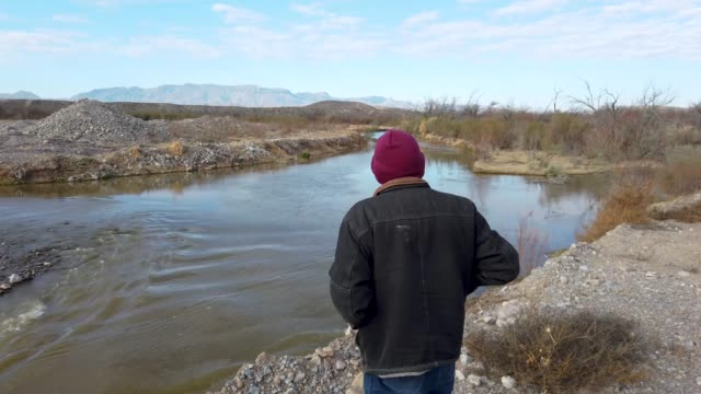 wayne talley walks along the bank of the rio grande river that borders his ranch and marks the border between mexico and the united states on january... - 国境点の映像素材/bロール