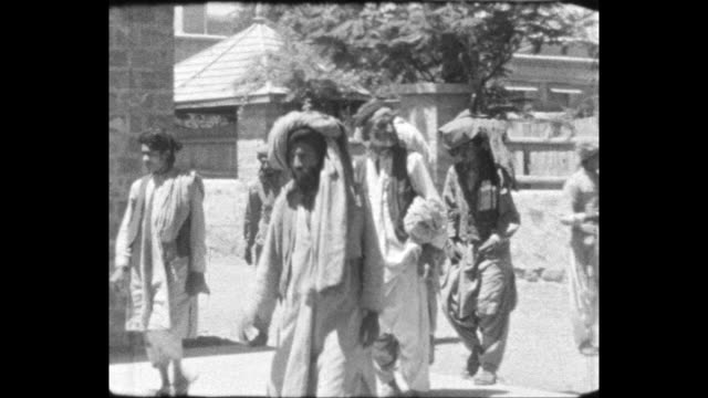 waziristan pashtun men walking past building indian soldiers in the british army standing on rooftop holding rifles - colonial stock-videos und b-roll-filmmaterial