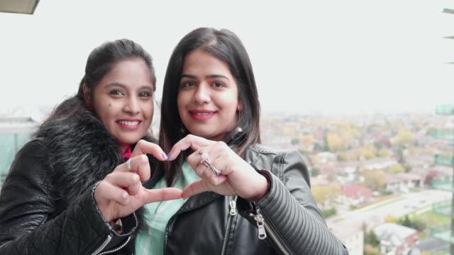 vídeos de stock, filmes e b-roll de estamos no amor - meninas fazendo forma coração usando as mãos - idade humana