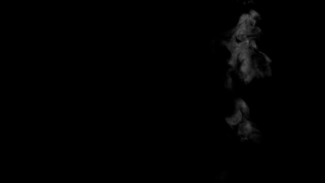 weak and narrow smoke or steam swirling on black background - steam stock videos & royalty-free footage