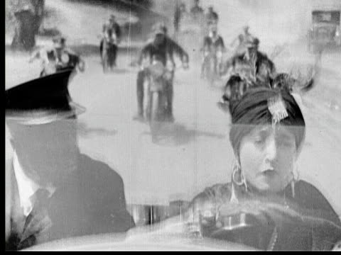 stockvideo's en b-roll-footage met 1925 b/w ms wealthy woman (madeline hurlock) driving convertible with man riding in passenger seat while motorcycle policemen chase them down road / los angeles county, california, usa - 20 29 jaar