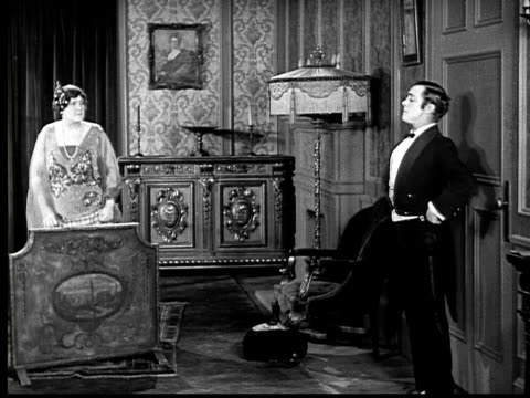 1924 b&w ws wealthy woman ordering frightened butler out the door  - collaboratore domestico video stock e b–roll