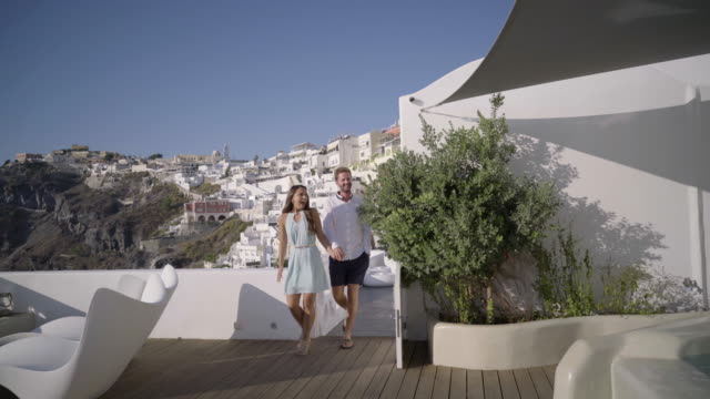 wealthy young tourist couple entering private terrace of hotel - insel santorin stock-videos und b-roll-filmmaterial