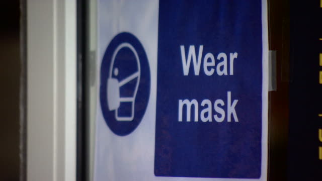 wear face mask signs due to coronavrius pandemic on public transport and shop windows in london - pandemic illness stock videos & royalty-free footage