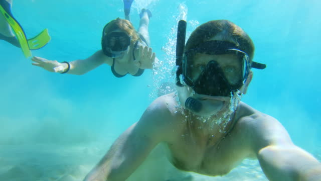 CU Wearable camera point of view couple snorkeling underwater in turquoise blue ocean
