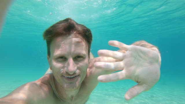 ms wearable camera point of view smiling man swimming underwater in turquoise blue ocean - emergence stock videos & royalty-free footage