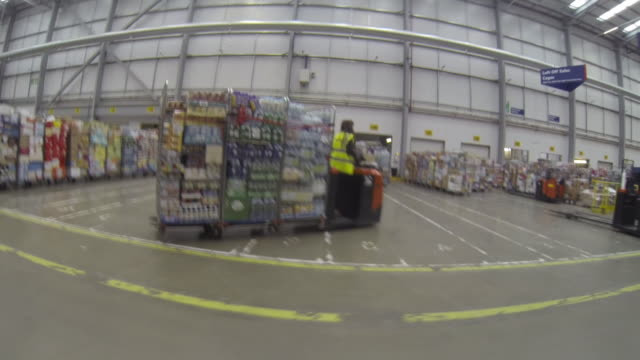 Wearable camera POV shot from a small forklift vehicle showing the periphery of a large food distribution warehouse in the UK.