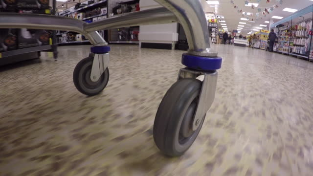 vidéos et rushes de wearable camera pov shot from the underside of a shopping trolley as it is wheeled around the non-food sections of a large uk supermarket (electrical appliances, homeware, clothing and detergent). - caddie