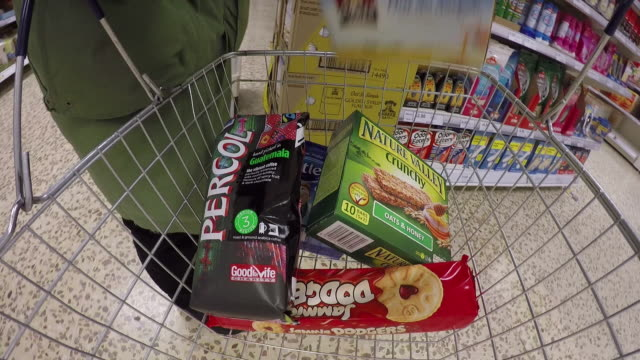 Wearable camera POV shot of a person adding breakfast foods, snacks, tea and coffee to a shopping basket at a large supermarket in the UK.
