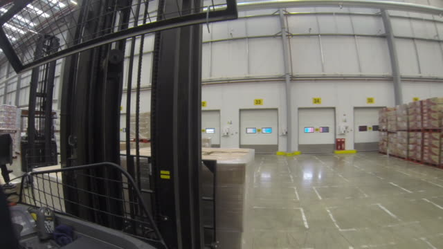 POV wearable camera shot reversing out from a loading bay through a large food distribution warehouse in the UK.