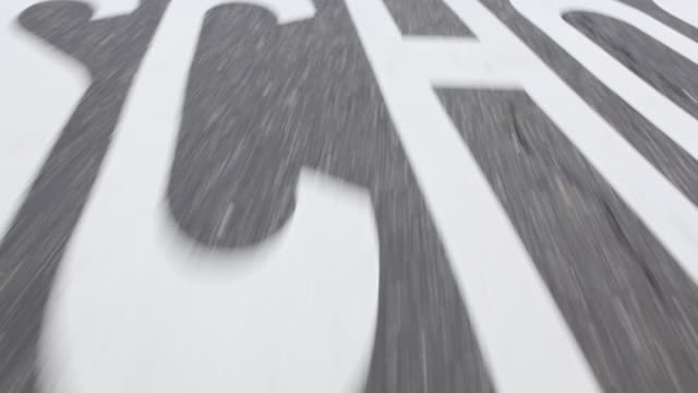 Wearable camera shot showing tarmac on a road including a marking reading 'SCHOOL', Long Island, USA.